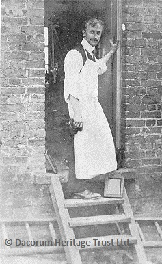 Edward Sammes at the door of his workshop on the corner of Wharf and Kingsland Roads.  There is a daylight printing frame on the steps.  This photo was taken by his fiancee, Ella Sharp | Dacorum Heritage Trust