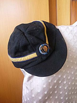 A black cap with a gold band with the motto 'Lumen Accipe et Impleat' or 'To Recieve Knowledge and Let it Grow' believed to be part of the Heath Brow Grammer School uniform circa 1885 | Helen Belcher