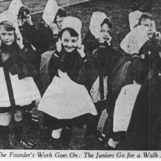 Foundling hospital junior children out for a walk. Girls wearing traditional uniforms of bonnet, cloaks and aprons. c.1937 | Berkhamsted Local History and Museum Society cared for by the Dacorum Heritage Trust