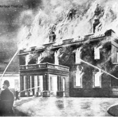 A rather fanciful depiction of the fire at Gaddesden Place which occurred on 1 February 1905.  Hemel Hempstead Brigade only had a horse-drawn manual engine, but Dickinson's Brigade had a 'steamer'.  Frogmore and Berkhamsted Brigades joined in the effort, but two of the staff died and the mansion burned for days. | Hemel Hempstead Local History and Museum Society cared for by the Dacorum Heritage Trust Ltd